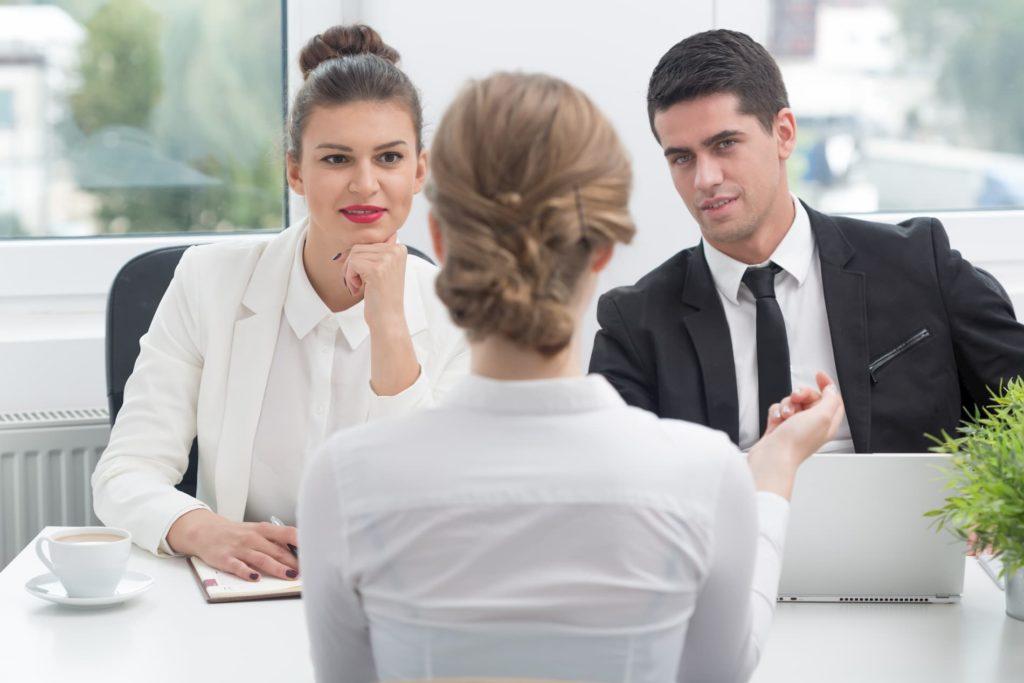 Eine Bewerberin im Vorstellungsgespräch mit zwei Angestellten