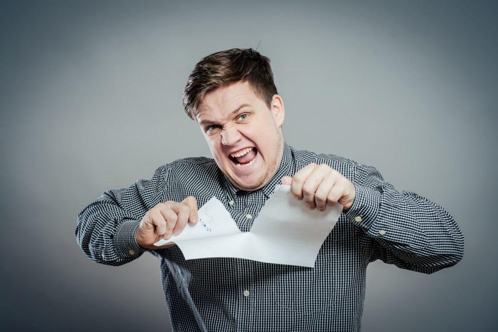 Ein Mann zerreißt ein Papier