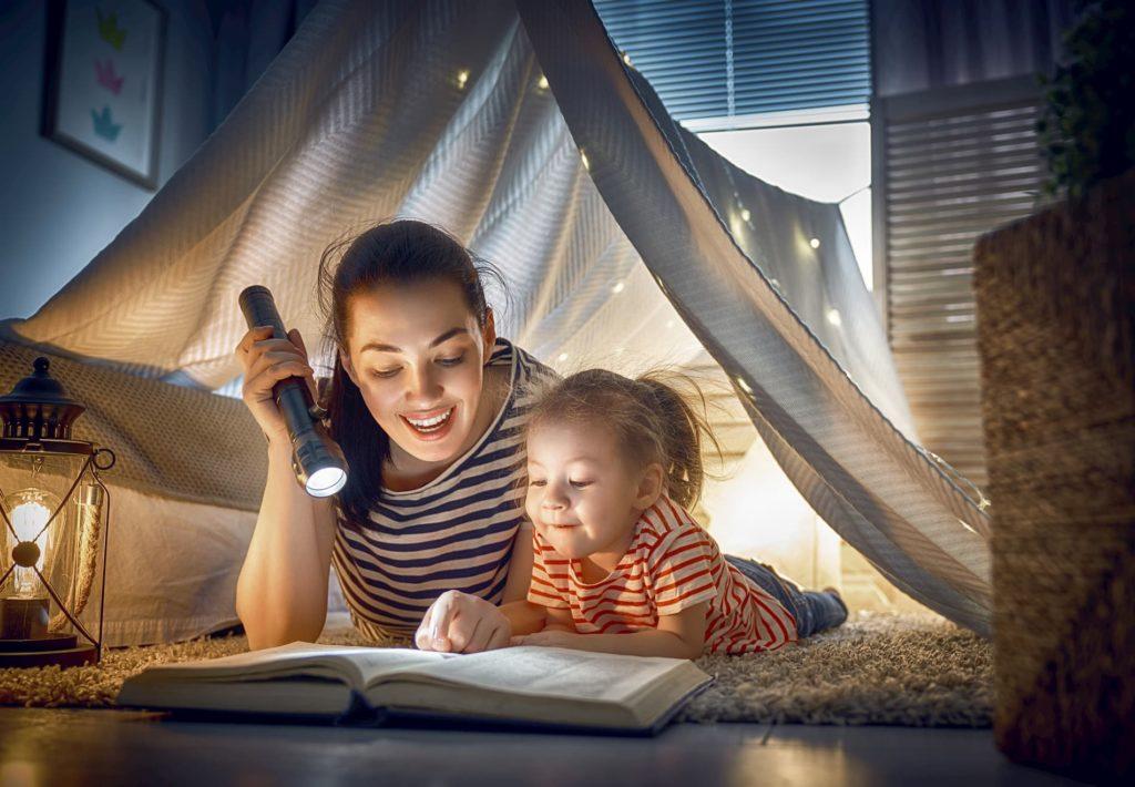 Elternzeit beantragen: Eine Frau liest mit ihrem Kind zusammen ein Buch