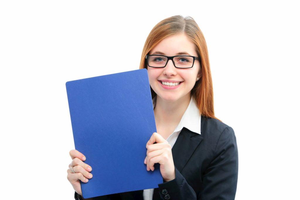 Eine Frau hält ihr Ausbildungszeugnis in den Händen