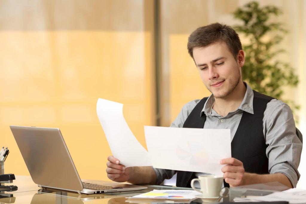 Ein Mann betrachtet Papiere vor dem Laptop