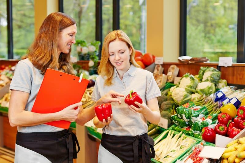 Eine ältere Mitarbeiterin hilft bei der Ausbildung im Einzelhandel