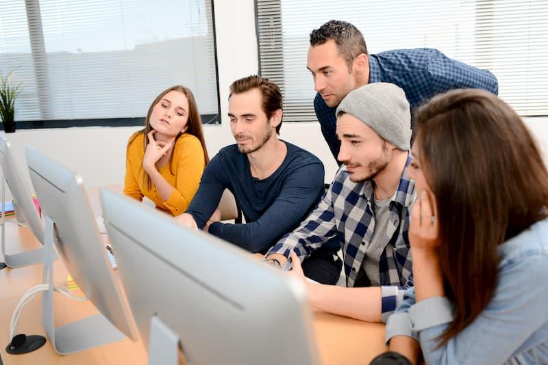 Junge Menschen sitzen vor einem PC und machen ein Traineeship