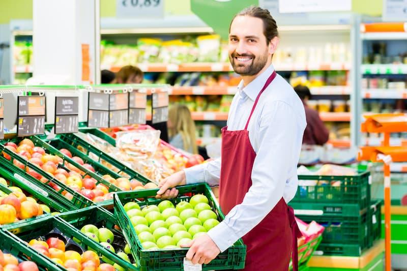 Ein beliebter Nebenjob ist das Auffüllen von Supermarktregalen, hier füllt ein Mann ein Regal mit Äpfeln auf