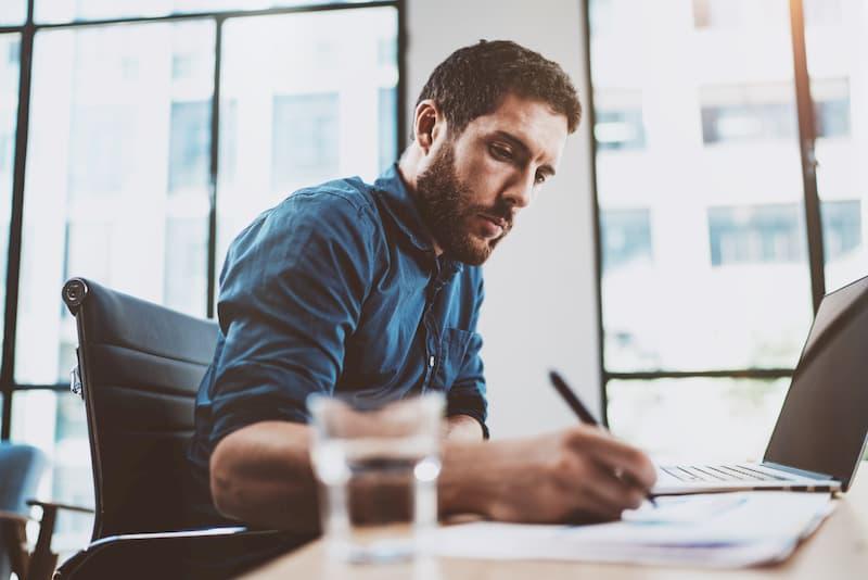 Ein junger Mann sitzt vor dem Laptop und führt nebenbei ein Berichtsheft