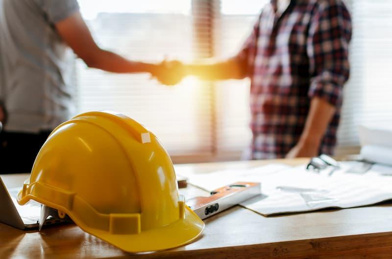 Ein Mensch schließt einen Arbeitsvertrag ab und ein Helm liegt auf dem Tisch