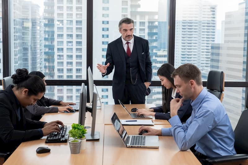 Ein Chef ist im Büro und erteilt seinen Mitarbeitern Anweisungen, dies darf er durch das Direktionsrecht