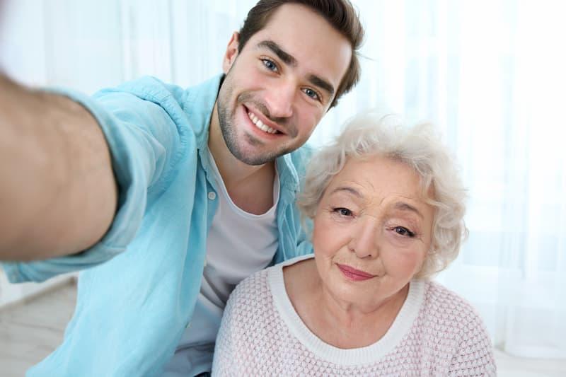 Ein junger Mann macht ein Selfie mit der Oma in der 4-Tage-Woche
