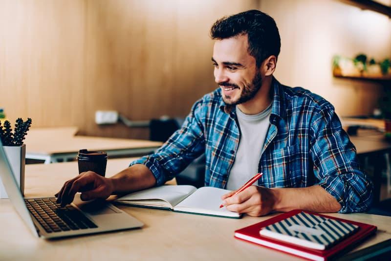 Ein Mann sitzt am Laptop und recherchiert mit einem Gehaltsrechner nach seinem Auskommen