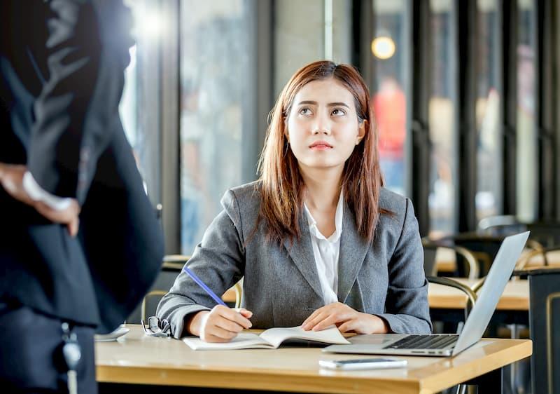 Eine Frau schaut traurig auf einen anderen Mitarbeiter nach einem Konflikt am Arbeitsplatz