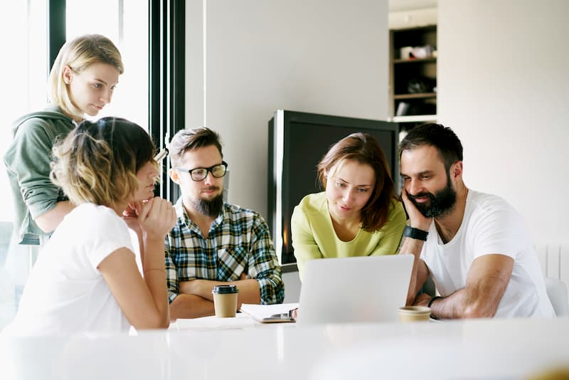Mehrere Mitarbeiter sitzen am Tisch bei einem Jour-Fixe