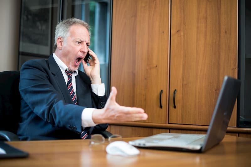 Ein Chef beleidigt einen Mitarbeiter am Telefon, ein Beispiel für Bossing