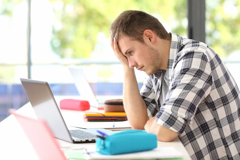 Ein junger Mann am Arbeitsplatz denkt darüber nach, seine Ausbildung abzubrechen