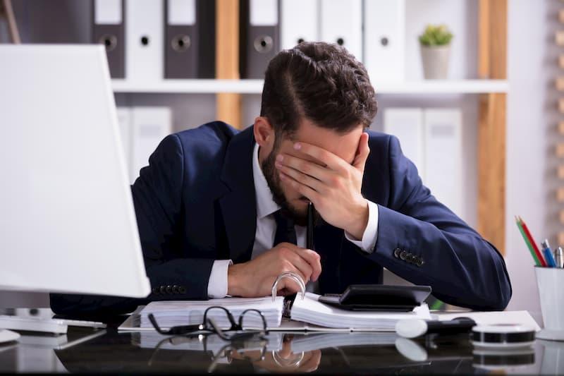 Ein Mann sitzt am PC und hält sich die Stirn, vielleicht kann ein Jobwechsel helfen