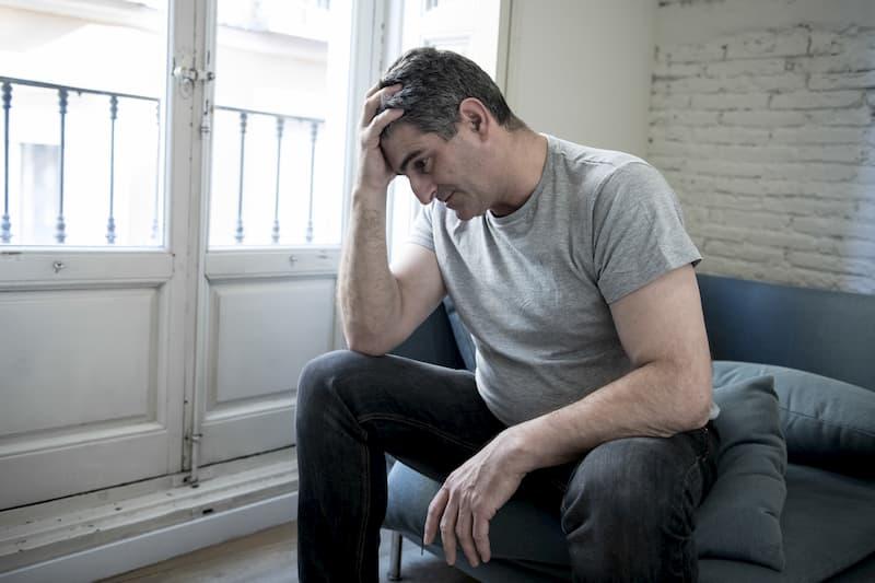 Ein Mann sitzt Zuhause und leidet am Burnout