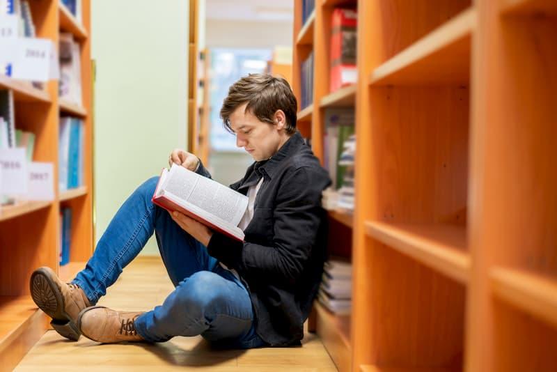 Ein Mann lernt im Rahmen der Bildungsteilzeit und liest ein Buch in der Bibliothek