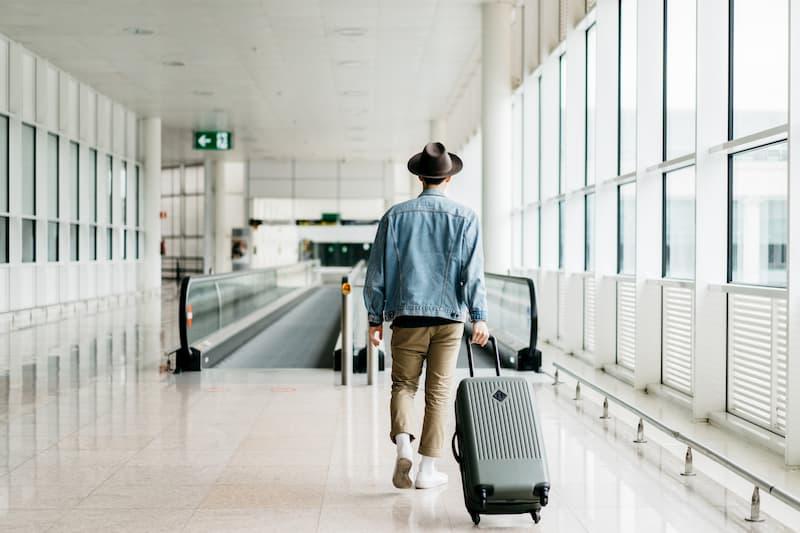 Ein Mann zieht seinen Koffer am Flughafen Richtung Terminal, er hat eine Urlaubsvertretung gefunden