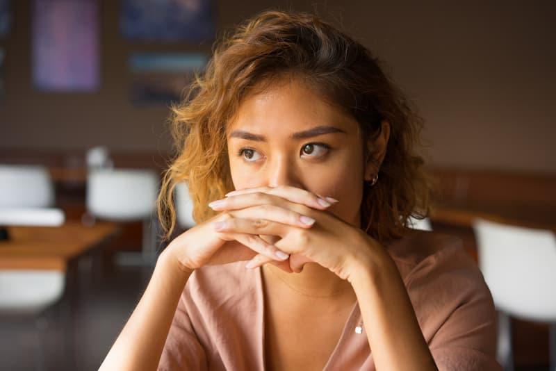 Eine Frau hält die Hände vors Gesicht und hat Selbstzweifel