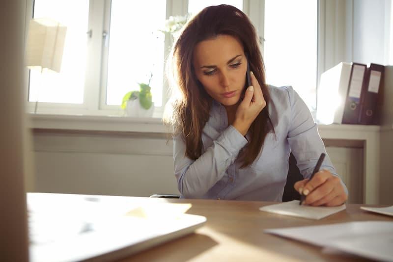 Eine Frau telefoniert auf der Arbeit privat und begeht Arbeitszeitbetrug