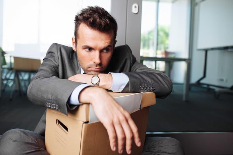 Ein Mann mit einem Karton sitzt im Büro und ist traurig über die fristgerechte Kündigung