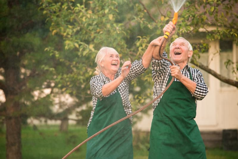 Eine Rentnerin und ihr Ehemann haben Spaß im Garten mit Gartenschlauch nach ihrem Renteneintritt