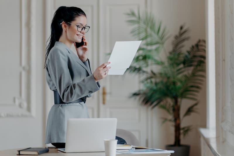 Eine junge Frau liest einen Brief und freut sich über eine Bonuszahlung