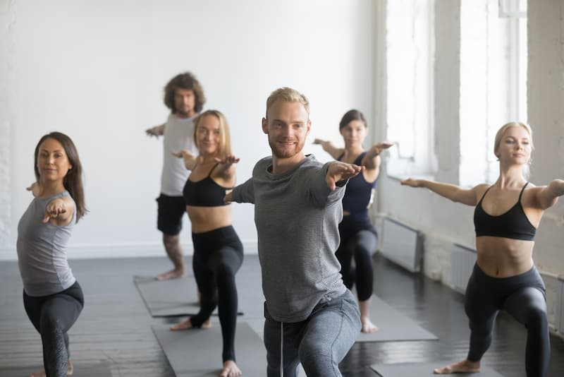 Kollegen machen zusammen einen Yoga-Kurs, dies gehört zu den Mitarbeiter-Benefits
