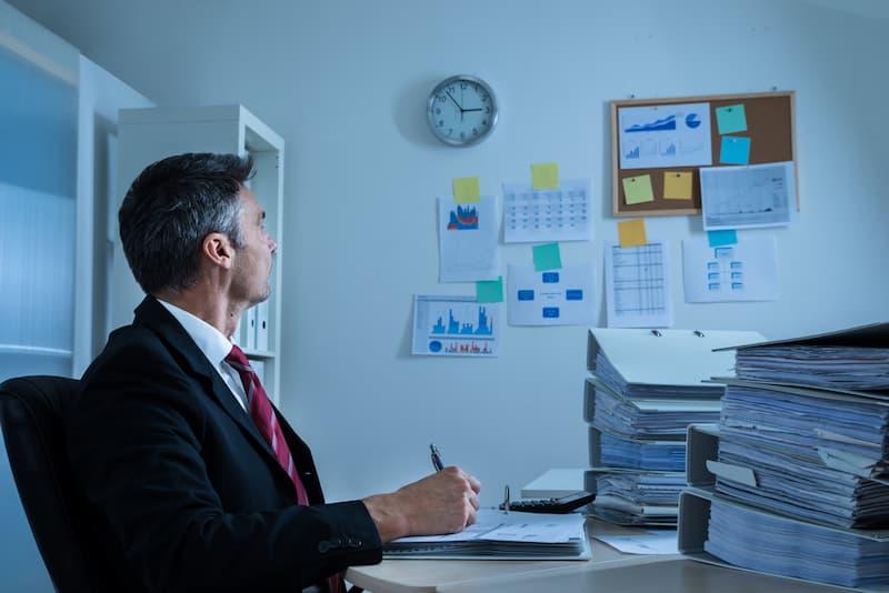 Ein Mann schaut auf die Uhr im Büro, da er sein Zeitmanagement verbessern möchte