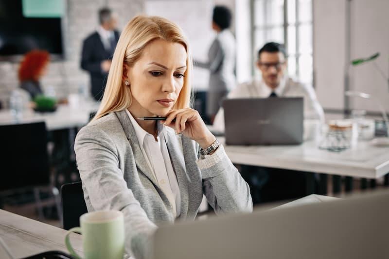 Eine Frau im Büro mit Sorgenfalten, sie hat eine Ermahnung erhalten