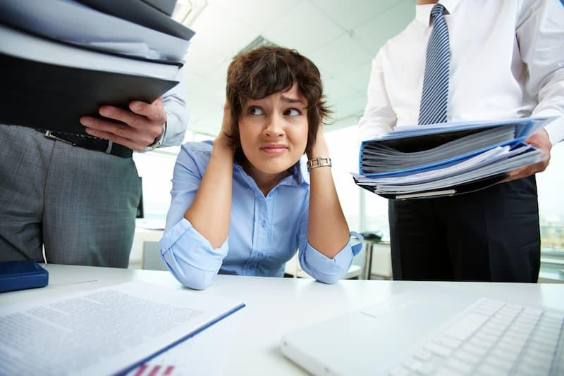 Eine Frau hält sich im Büro die Ohren zu, sie leidet unter Beleidigungen am Arbeitsplatz