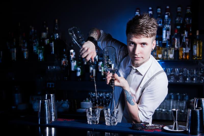 Ein Mann hat einen Zweitjob als Barkeeper und steht hinter der Theke