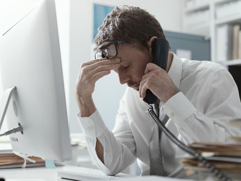 Ein Mann ist am Schreibtisch im Büro gestresst durch die Doppelbelastung von Familie und Beruf