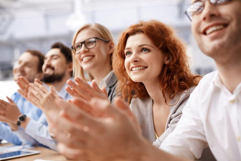 Mitarbeiter klatschen und freuen sich über zusätzliches Geld, dies kann ein Teil einer betrieblichen Übung sein