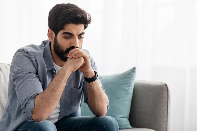 Ein Mann sitzt auf dem Sofa und denkt nach, denn er hat Bewerbungsangst