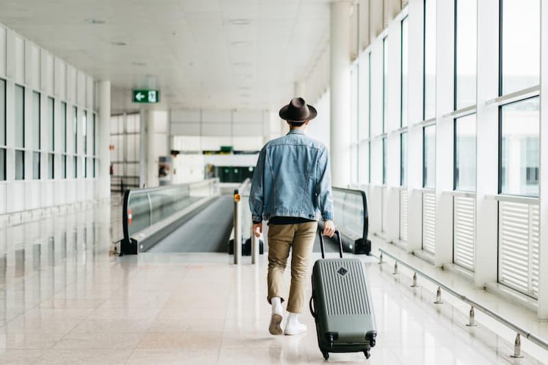 Ein Arbeitnehmer mit Koffer am Flughafen, wieviel Mindesturlaub hat er?