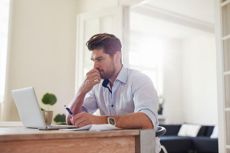 Ein Mann sitzt vor dem Laptop und ist bei der Jobsuche