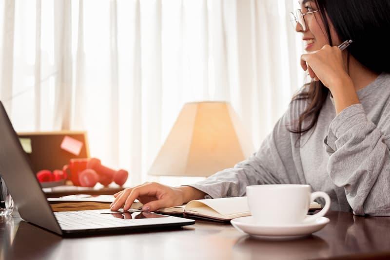 Eine Frau ist arbeitslos und sucht am Laptop einen Job
