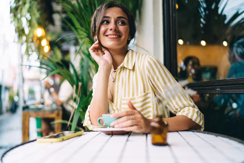 Eine Frau sitzt im Cafe und hat Rufbereitschaft