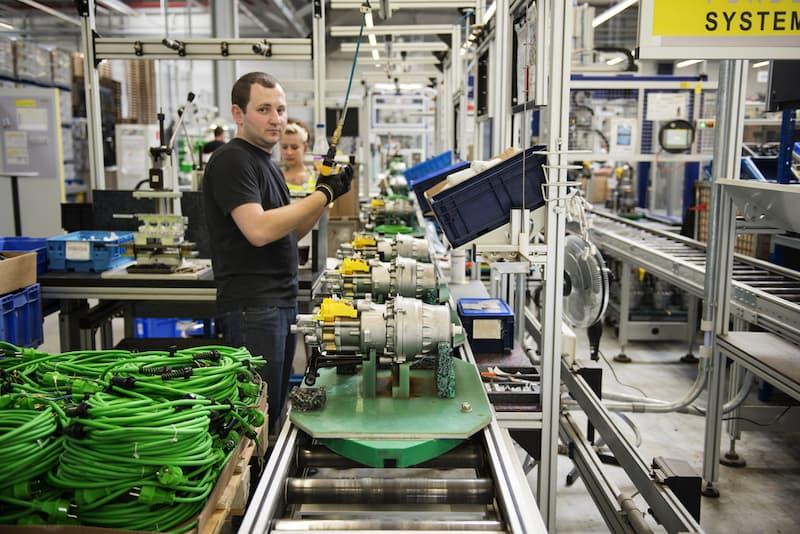 Ein Mann arbeitet an einem Fließband in Schichtarbeit