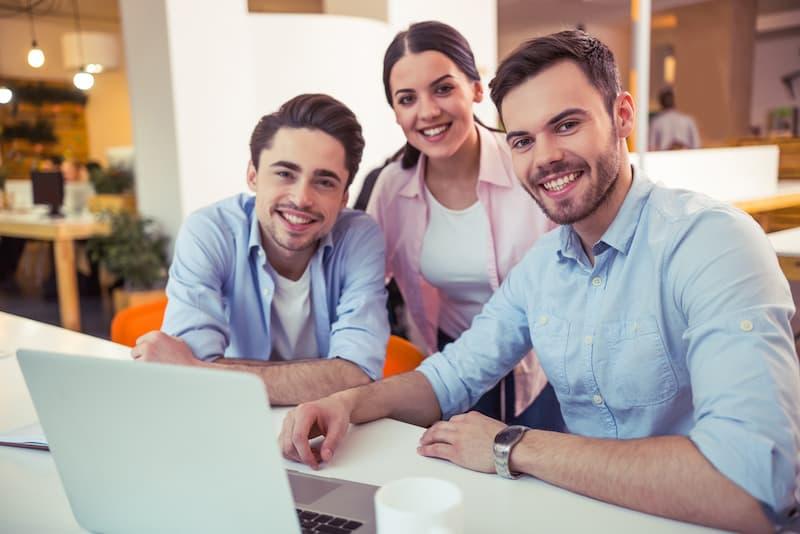 Menschen sitzen glücklich vor einem Laptop, es gibt eine hohe Mitarbeiterzufriedenheit