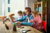Ein Mann sitzt mit Kindern und Katze am Schreibtisch, ein Beispiel für Work-Life-Blending