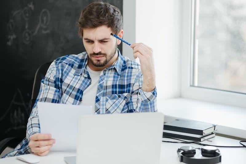 Ein Mann liest sein Zeugnis durch und rätselt über die Zeugniscodes