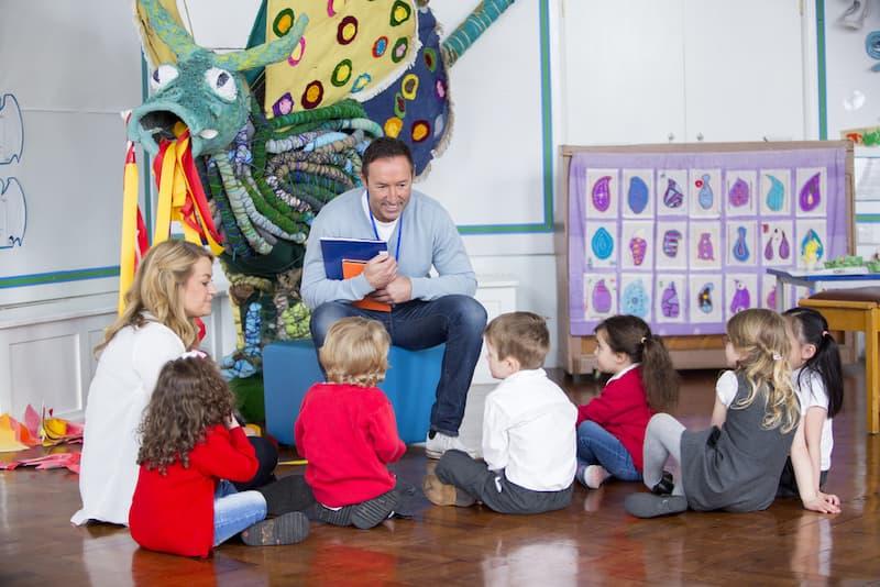 Ein Mann sitzt vor Kindern nach der Umschulung zum Erzieher