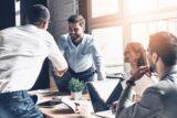 Ein Mann wird von seinen Kollegen begrüßt nach einem Arbeitsplatzwechsel innerhalb der Firma