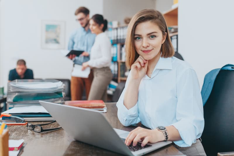 Eine Frau nach der Umschulung als Bürokauffrau am Schreibtisch mit Laptop
