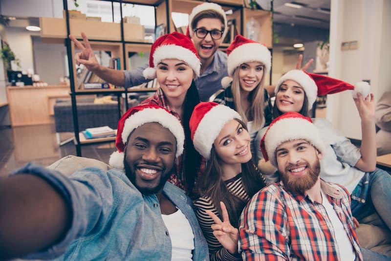 Mehrere Mitarbeiter mit Weihnachtsmützen, sie erhalten Weihnachtsgeld